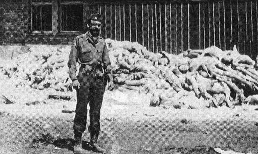 """This picture shows me, Capt. Alfred de Grazia, in front of a pile of dead bodies at Dachau concentration camp in Bavaria Germany, two (maybe three) days after the liberation of the camp by the American army. I was then Commanding Officer of the Psychological Warfare Combat Propaganda Team attached to HQ, the Seventh Army."" (Wikimedia Commons)"