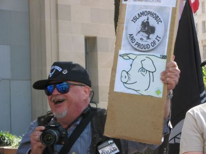 Protester holding a sign in Washington, D.C. Original caption: Sept 15 2007 March and Rally, Member of the counter protest Gathering of Eagles, yelling